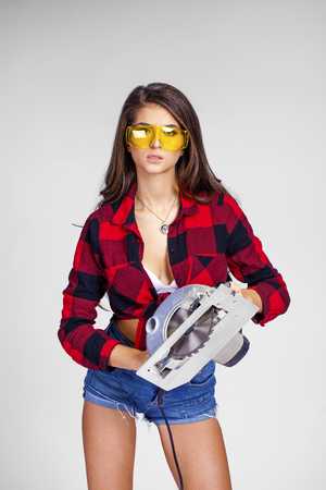 Project Satisfaction. Beautiful sexy brunette woman in goggles with a circular saw, isolated on white background Stock Photo