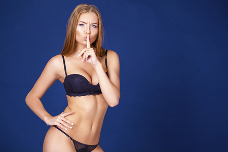 requires: Sexy Woman requires silence. Young beautiful blonde has put forefinger to lips as sign of silence, isolated on blue Stock Photo