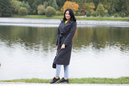 Young beautiful brunette woman in gray coat on the autumn embankment park