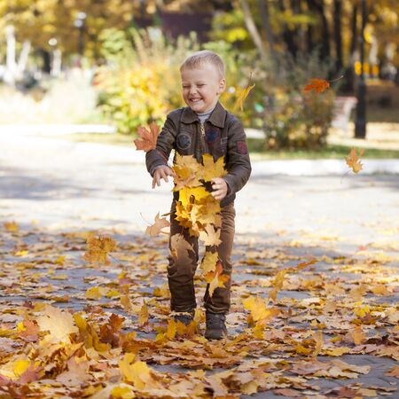 Portrait of a young boy in pilot leather jacket in autumn park