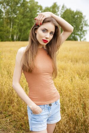 Young beautiful brunette woman in Oats field, summer outdoors