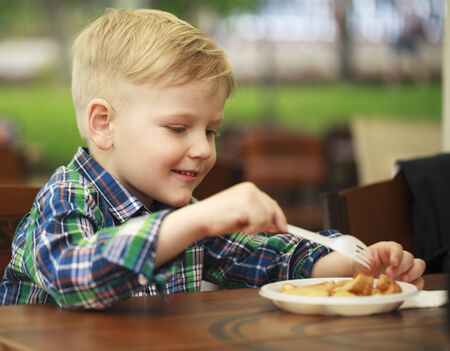 5s: Blonde little boy eating fried potatoes at a cafe, food concept