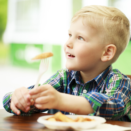 Blonde little boy eating fried potatoes at a cafe, food concept