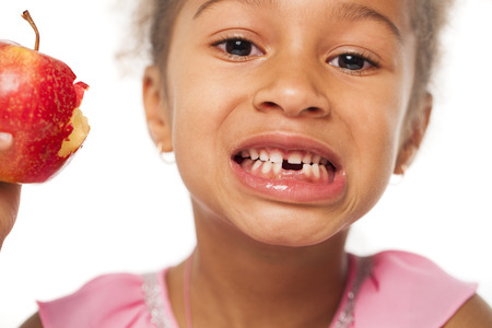 Ð¡alfs teeth, Portrait of a pretty little girl with a red apple on white background Stock Photo