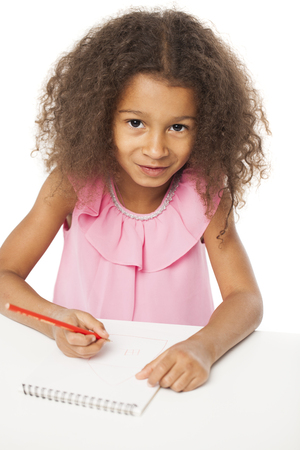 brazilian ethnicity: Education. Close up portrait of african little girl is sitting at the table with a notebook for drawing, isolated on white background Stock Photo