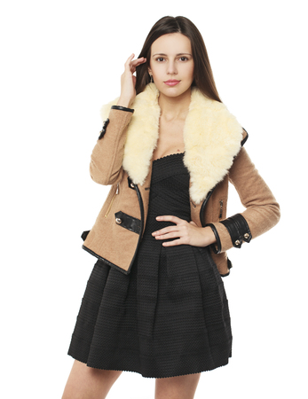 Young beautiful brunette woman in stylish in beige sheepskin coat, isolated on white background Stock Photo