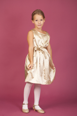 Beautiful blonde little girl in golden dress, isolated on plum background
