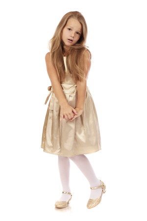 Beautiful blonde little girl in golden dress, isolated on white background Stock Photo