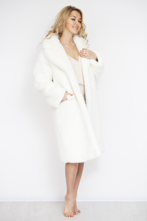 Young beautiful blonde woman in white fur coat in show room Stock Photo