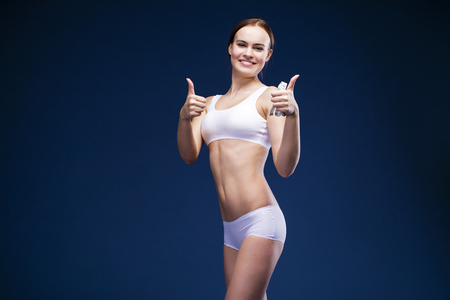 Young beautiful woman in a white sports underwear, isolated over dark blue background Stock Photo