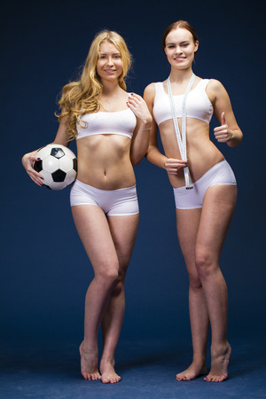 Happy girls holding a soccer ball. Two Young beautiful women in white fitness clothing, dark blue isolated background Standard-Bild