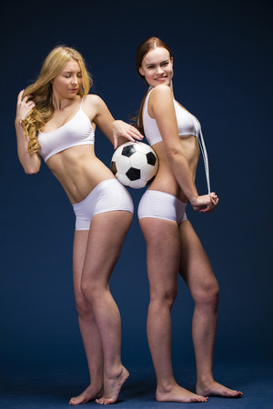 Happy girls holding a soccer ball. Two Young beautiful women in white fitness clothing, dark blue isolated background Stock Photo
