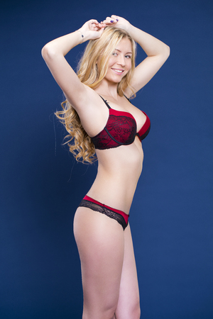 Portrait of sexy blonde woman in red underwear on a dark blue wall studio 스톡 콘텐츠