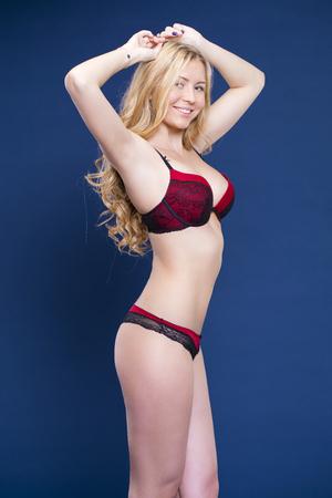 Portrait of sexy blonde woman in red underwear on a dark blue wall studio Archivio Fotografico