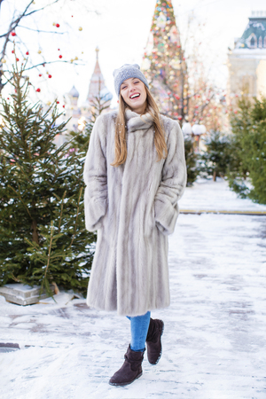 Portrait of a young woman in a blue knitted hat and gray mink coat, posing in winter Red Square in central Moscow Stock Photo