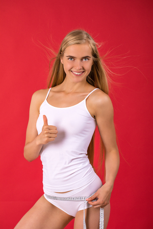 Fit and sporty blonde woman posing over red background. Sport, fitness, diet, weight loss and healthcare concept
