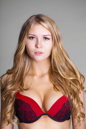 Happy young blonde woman posing in red bra over gray background Stock fotó