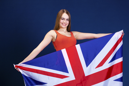 Young beautiful girl holding a large flag of Great Britain, dark blue studio background Banque d'images