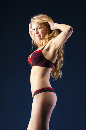 Sexy young blonde woman posing in red bikini over dark wall background Archivio Fotografico