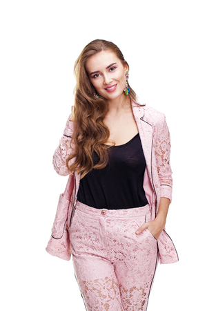 Fashion portrait of a beautiful young woman in pink lace jacket posing at studio isolated on white background