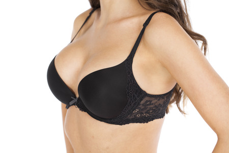 Body part sexy female breast in black bra, isolated on a gray background