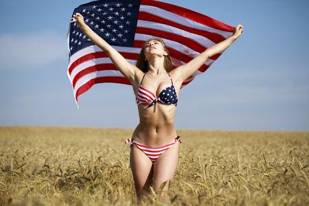 Jeune belle femme blonde en bikini de drapeau américain sexy dans un champ de blé Banque d'images