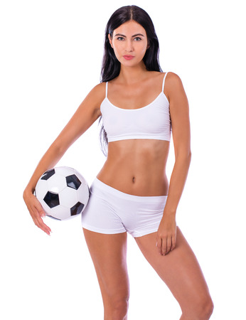 Fitness model holding a soccer ball. Young beautiful brunette woman in sporty clothing, on white isolated background Stock Photo