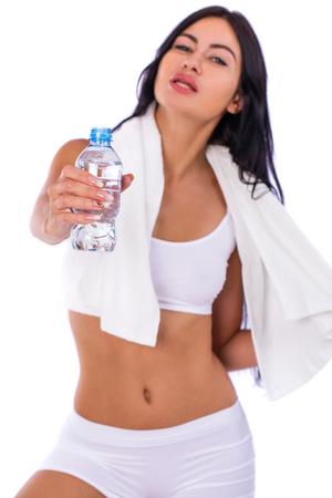 Fitness diet, young beautiful brunette woman in a sporty white clothes drinking water from a bottle, isolated on a white background