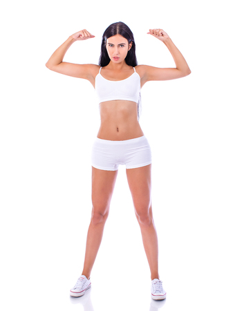The strength of a woman in her weakness. Weight loss and healthcare concept. Strong beautiful brunette girl in white fitness clothing
