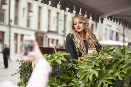 Young happy blonde woman drinking cocktail in a cafe, street outdoors Stock Photo