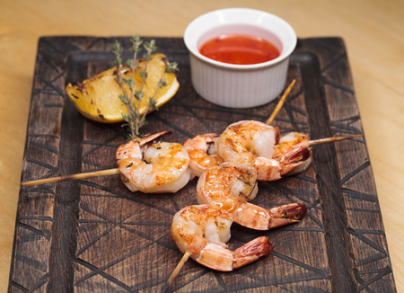 Close up royal prawns on skewers, cooked on a grill with tomato sauce