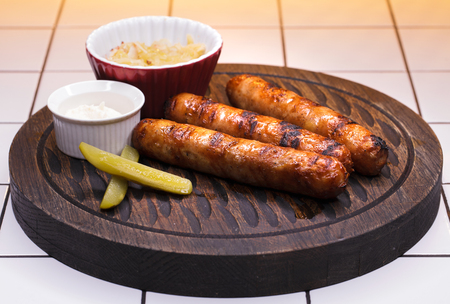 Restaurant dish. Three grilled sausages on a wooden tray Stock fotó