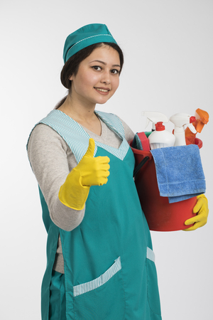 Young woman holding cleaning tools and products in bucket, isolated on white background Stock Photo