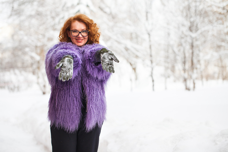 Adult beautiful woman in llama fur coat posing against the background of a snow-covered winter park Stock Photo
