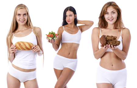 Three beautiful slender girls in sports lingerie with bread and vegetable salad - isolated on white background