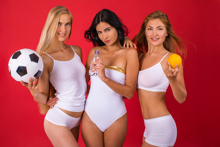 Fitness women. Three young beautiful girlfriends in white sportswear isolated on red background
