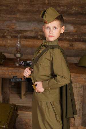 Russian boy in the old-fashioned Soviet military uniform with a binoculars on the background of a dugout from the bars Stock Photo
