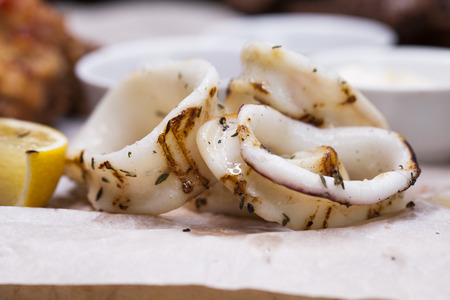 Restaurant dish - grilled squid rings on a wooden board with sauce Foto de archivo
