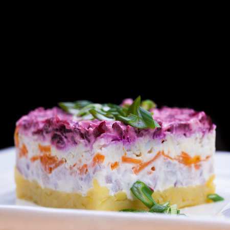Russian food: holiday herring salad with vegetables close-up on the table