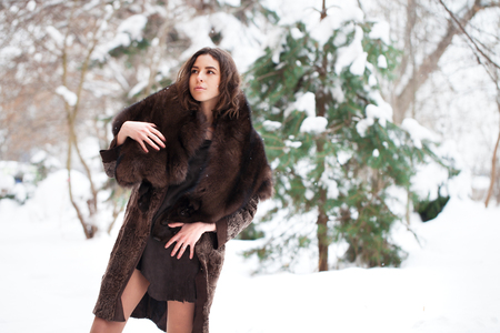 Young beautiful brunette woman in fur coat posing on winter park. Model wearing stylish warm clothes.