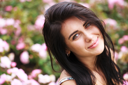 Portrait of a beautiful young woman on a background of spring flowers park 스톡 콘텐츠