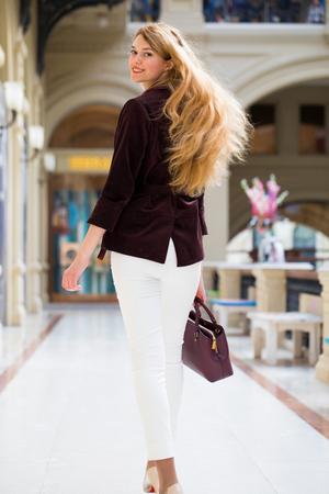 Young beautiful blonde woman in a corduroy jacket walking in a shopping center