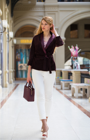 Full-length portrait, young beautiful blonde woman in white pants and corduroy jacket walking in the shop Archivio Fotografico
