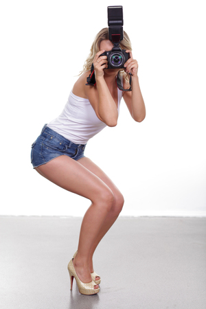 Young sexy woman is a professional photographer with slr camera Standard-Bild