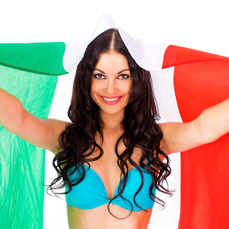 Young beautiful brunette woman in blue bikini holding a large flag of Italy, isolated on white background Stock Photo