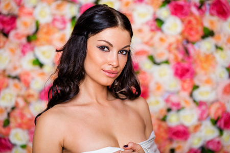 Closeup portrait of a beautiful young brunette woman in a studio on a floral wall background Stock Photo