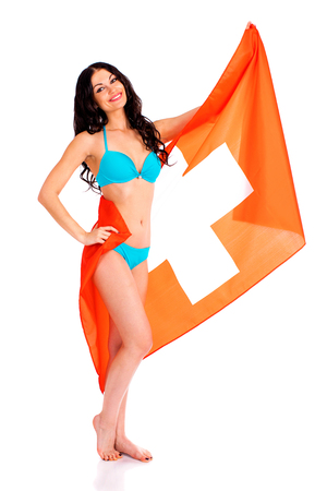 Young beautiful brunette woman in blue bikini holding a large flag of Switzerland, isolated on white background