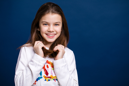 Happy brunette little girl, isolated on dark blue background