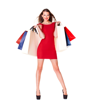 Young beautiful brunette woman in red dress with some shopping bags, isolated on white background Stock Photo