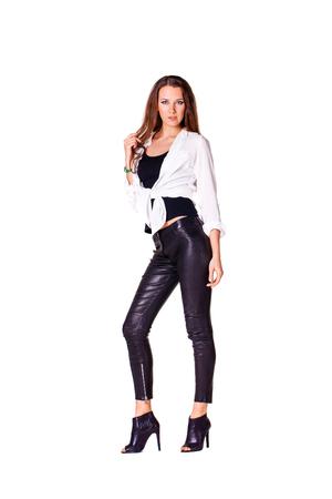 Elegant glamour brunette woman wearing blouse and black leggins, isolated on white background Stock Photo